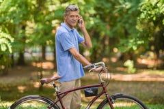 Homme aîné avec la bicyclette Image stock