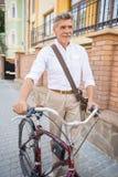 Homme aîné avec la bicyclette Images stock