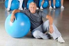 Homme aîné avec la bille de gymnastique dans la forme physique Photo stock