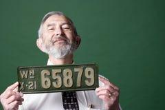 Homme aîné avec la plaque minéralogique photo stock