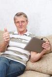 Homme aîné avec le dispositif de tablette. Le pouce est vers le haut Photo libre de droits