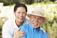 Homme aîné avec le fils adulte dans le jardin Photographie stock