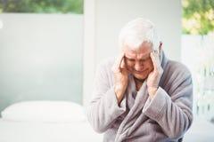 Homme aîné avec le mal de tête Images stock
