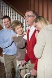 Homme aîné avec le marcheur à la maison avec la famille Image stock