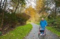 Homme aîné avec le marcheur en stationnement Image libre de droits
