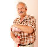 Homme aîné avec le rouleau de peinture Photo libre de droits