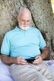 Homme aîné avec le téléphone intelligent Photos libres de droits