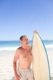 Homme aîné avec sa planche de surfing Photos libres de droits