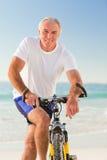 Homme aîné avec son vélo Photos stock