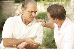 Homme aîné ayant le fils sérieux d'adulte de conversation Image stock