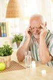 Homme aîné ayant le mal de tête Photos stock