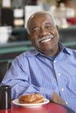 Homme aîné ayant le thé de matin Images stock
