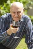 Homme aîné bel appréciant une glace de vin rouge Photo stock
