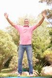 Homme aîné branchant sur le tremplin dans le jardin Photo libre de droits