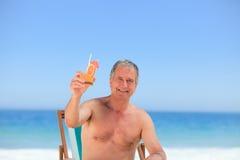 Homme aîné buvant un cocktail sur la plage Photo libre de droits