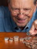 Homme aîné comptant l'argent comptant dans des piles Image libre de droits