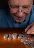 Homme aîné comptant l'argent comptant dans des piles Photo stock