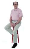 Homme aîné confiant se reposant sur des selles Photos libres de droits