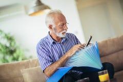 Homme aîné contrôlant à la maison des finances photos libres de droits