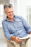 Homme aîné détendant à la maison avec un livre Image stock