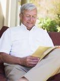 Homme aîné détendant avec le livre Images libres de droits