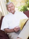 Homme aîné détendant avec le livre Image stock