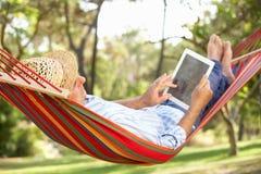 Homme aîné détendant dans l'hamac avec l'E-Livre Images stock