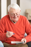 Homme aîné détendant dans la présidence à la maison Photographie stock libre de droits