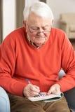 Homme aîné détendant dans la présidence à la maison Images libres de droits