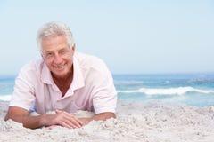 Homme aîné détendant sur la plage sablonneuse Photos stock