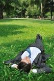 Homme aîné d'affaires détendant dans l'herbe Images stock