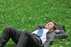 Homme aîné d'affaires détendant dans l'herbe Photos libres de droits