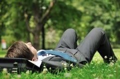 Homme aîné d'affaires se situant dans l'herbe Photos libres de droits