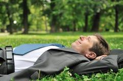 Homme aîné d'affaires se situant dans l'herbe Image libre de droits