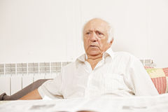 Homme aîné dans la chemise blanche avec le journal Photographie stock