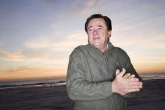 Homme aîné dans le chandail à l'aube sur la plage Photo libre de droits