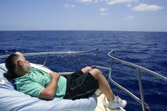 Homme aîné de marin ayant un reste sur le bateau d'été Photographie stock