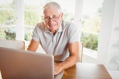 Homme aîné de sourire à l'aide de l'ordinateur portatif Images stock