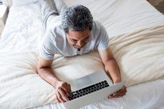Homme aîné de sourire à l'aide de l'ordinateur portatif Photos libres de droits