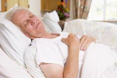 Homme aîné en sommeil dans le bâti d'hôpital Image stock