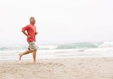 Homme aîné en vacances fonctionnant le long de la plage Image libre de droits