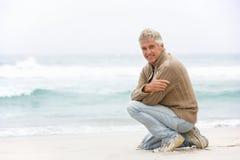 Homme aîné en vacances se mettant à genoux sur la plage de l'hiver Images libres de droits