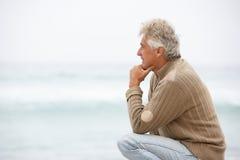 Homme aîné en vacances se mettant à genoux sur la plage de l'hiver Photographie stock libre de droits