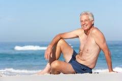 Homme aîné en vacances se reposant sur la plage sablonneuse Photo stock