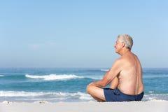 Homme aîné en vacances se reposant sur la plage sablonneuse Image libre de droits