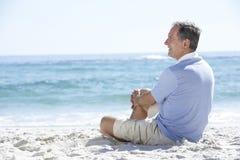 Homme aîné en vacances se reposant sur la plage sablonneuse Images stock