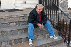 Homme aîné entre deux âges s'asseyant sur des escaliers d'église Photos libres de droits