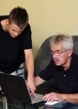 Homme aîné et adolescent sur l'ordinateur portatif Photos libres de droits