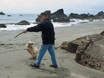 Homme aîné et crabot sur la plage Images libres de droits