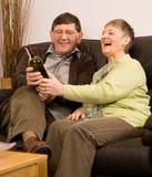 Homme aîné et femme détendant avec du vin Image libre de droits